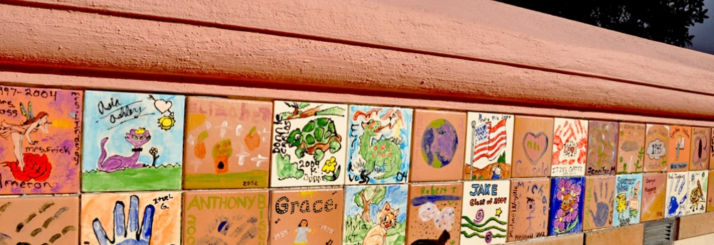 Wall with student-painted tiles outside the school