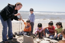 undergraduate female teaches kids on the beach