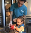 apprentice works with a child at MOXI